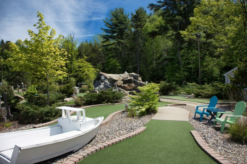Golfers crossing mini golf in rockport maine - showing boat and course for mini golf